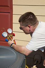 air conditioning technician checking refrigerant pressure