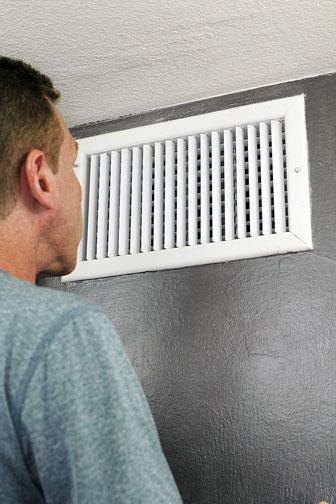 man inspecting an HVAC duct register